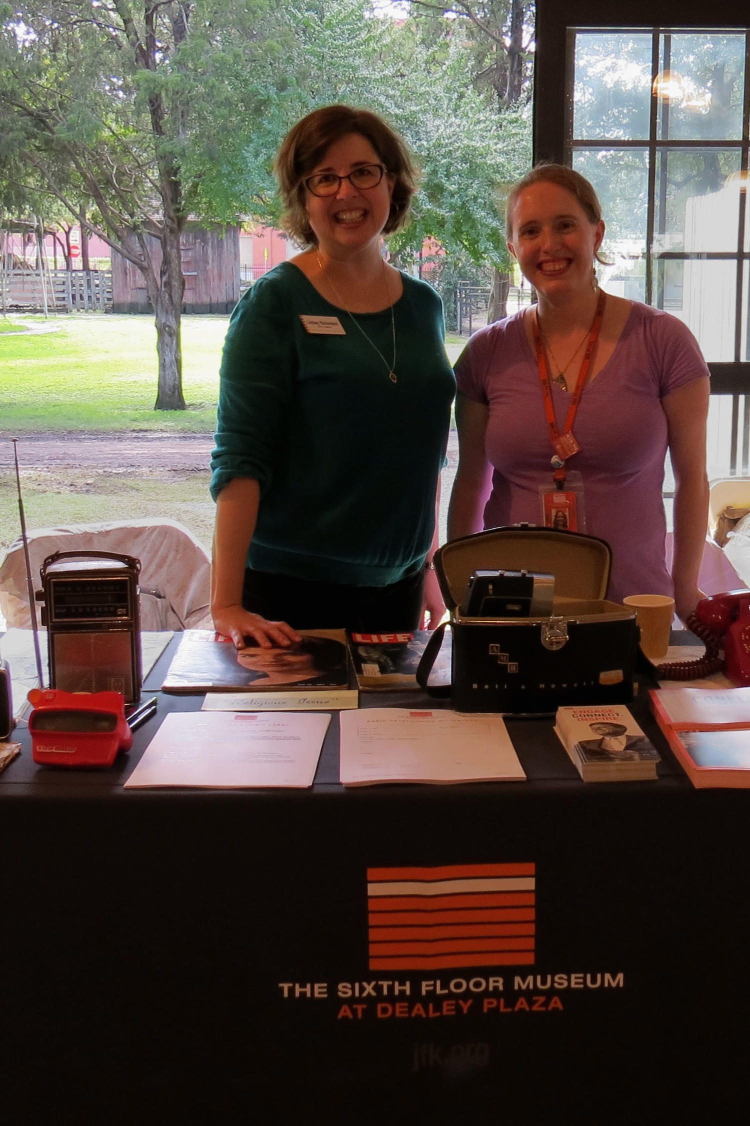 [Lindsey and Stephanie at Sixth Floor Museum table], Photograph of Lindsey Richardson (green), the Curator of Collections, and Stephanie Allen-Givens (purple), the Collections and Exhibits Manager, standing behind the Sixth Floor Museum display table. A visitor is standing in front of them and on the table are radios, a purse, a telephone, LIFE Magazine, other artifacts from the time-period and several paper handouts on the table for visitors.,