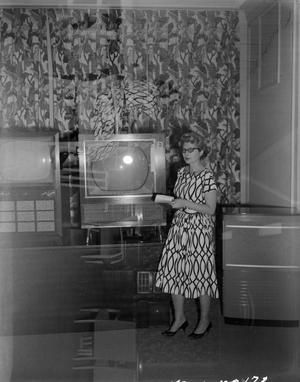Primary view of [Marie Stevenson standing next to a television]