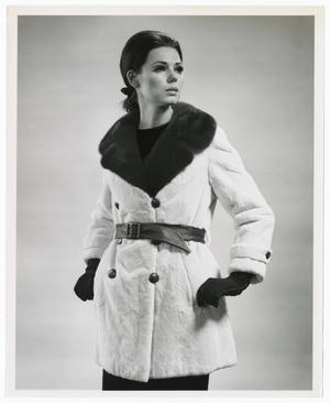 Black and white photo of a white woman wearing a white furn pea coat, with a black belt around the waist. The collar of the coat is black fur, and black buttons are on the front and wrists. She wears black gloves and looks to the right.