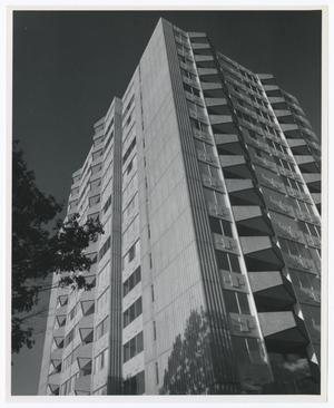 Black and white photograph of a tall skyscraper taken from it's base, at a corner looking upward. The building has triangular awnings going up each visible side in two columns. A small section of a tree is visible to the far left.