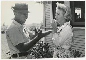 Black and white photograph of a latinx man and white woman standing outside. Part of a house with windows and bushes can be seen behind them. They face each other both smiling and moving their hands and arms in conversation.