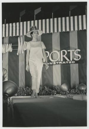 Black and white photo looking up at runway model wearing all white t-shirt and pants, with a large wide-brim hat. Behind her a sign says Neiman Marcus, Sports Illustrated.