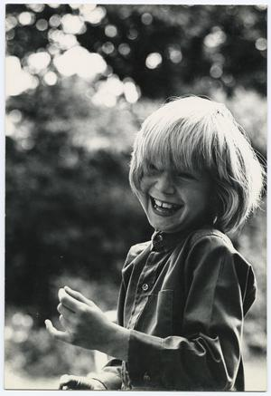 Black and white photo of a young boy with shoulder length blond hair and straight bangs. He is visible from the waist up, and is smiling and moving his arms in front of him. Pixilated tree top shapes are visble in the background.