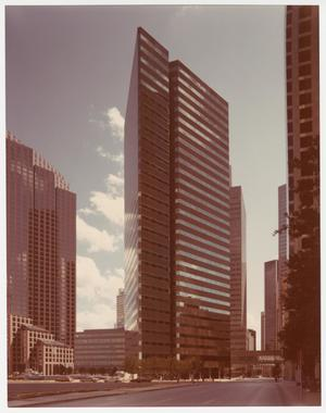 Color photograph of a large skyscraper, taken from street level. The building looks triangular, and rows of uninterrupted windows wrap around the building. Other skyscrapers are visible to the left and right of the building, and more can be seen in the background.