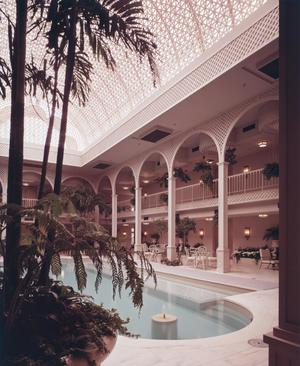 Color photograph of a pool inside a large room, with a long skylight above. Tables and chairs are along the edge of the pool, next to columns that go up to the second floor with a railing around it. A potted tree is in the foreground taking up the left half of the photo.