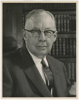 Black and white portrait of an older white man. He is visible from the chest up, wears a dark suit and tie, with horn rimmed glasses. Behind him are shelves of sets of books.