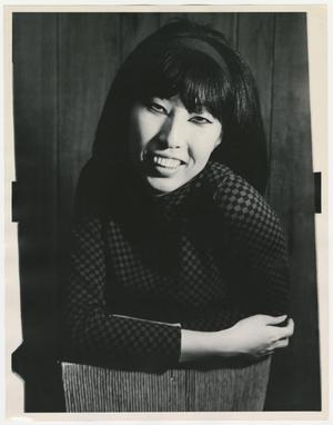 Black and white portrait of an Asian woman. She had long dark hair and straight bangs. She is sitting backwards on a chair, with one arm resting on the top of the chair. She wears a dark checkered shirt and smiles at the camera.