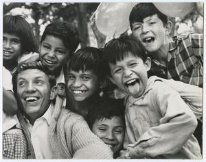 Black and white photo with a group of kids and a man all close together making faces and smiling. The man is in the lower left corner with the children surrounding him. Two balloons are visible in the top right corner, and tree tops are visible along the top edge.