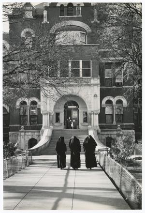 Black and white photo looking down a paved walkway that leads to the doors of a large brick building, with arches above the door and windows. Three nuns are walking towards the building, nearing the steps. There are low chain-link fences along either side of the walkway.