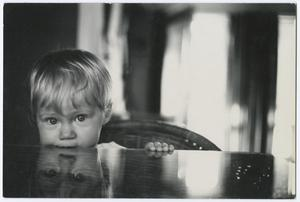 Black and white photograph of a baby sitting at a table, with only their head and one hand visible. The baby has its mouth on the edge of the table, and looks directly into the camera. A clear reflection of their face can be seen in the table top.