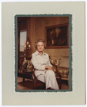 Color photograph of an older white woman sitting in a wood chair. She wears a white pant suit, and has her legs crossed at the knee. Behind her is a floral print couch, large decorative lamp, and a painting on the wall. The photo is matted with an off white border.