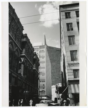 Black and white photo looking slightly upward from street level between two six-story buildings. People and a car are visible on the street, and a large building can be seen behind and between the two closer buildings.