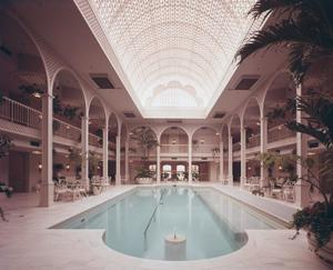 Color photo at the end of a long pool in a large room. An arched skylight spans the length of the pool. Large archways reveal the second floor on all sides of the room, and tables and chairs and large potted trees are places around the pool on the first floor.