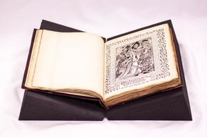 An open book is shown. On the left side is a blank page. On the right page is a page filled with a design and a drawing printed on it.
