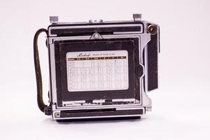 An old black Linhof Camera. It is seen on the back with a depth scale on it.