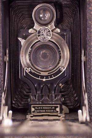 A close up of a black Kodak camera. The closeup is of the camera lens, with the camera name on it in small letters.