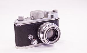 A side view of the front of a Robot II camera. It is black and silver with the lens uncapped.