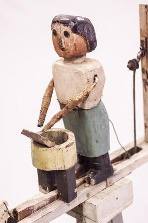 Wooden figure of a woman washing clothes. She has a grey skirt and white shirt painted on. Her arms are sticks extended out to a barrel-like thing standing in front of her with a small piece of wood in it representing a piece of clothing.