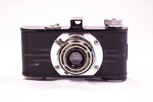 A black Argus camera seen from the front. The lens is silver, with the words Argus on it in small letters.
