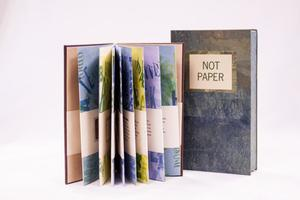 "A book titled ""Not Paper"" in a white block on the front of the cover, with the rest being a marbled blue. Next to it on the left is an open book. The pages are different colors."