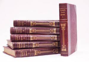 A stack of five books with another book propped up against it. The books are all a deep red with a gold design and gold lettering.