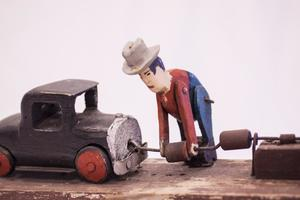 Close up of a tin man with a tin truck to the left of him. The man has blue pants, a red shirt and hat. The truck is black with red on the wheels. The tin man is bending over and holding onto something attached to the truck.