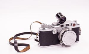 The front of a Leica Camera. It is black, but the top of it is silver. The camera lens is covered with a silver cap. Attached to it is a leather handle.