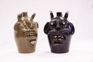 Olive colored jug shaped like a devils face on the left and the black jug shaped like a devils face on the right. They are both shiny, but have some pieces chipped off from the horns. They are perfectly alike except for the color.