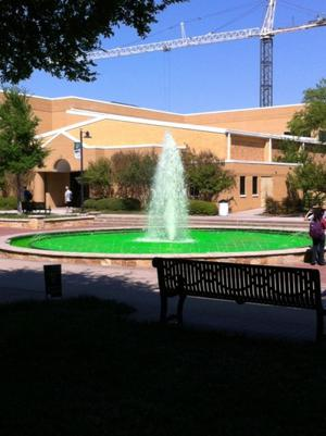 Color photograph of a fountain with the water dyed green. A building a crane are in the background.