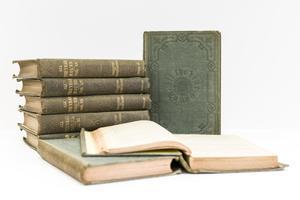Una pila de cinco libros está a la izquierda. Un libro en posición vertical está al lado de la pila, un libro abierto está encima de un libro cerrado delante de la pila.