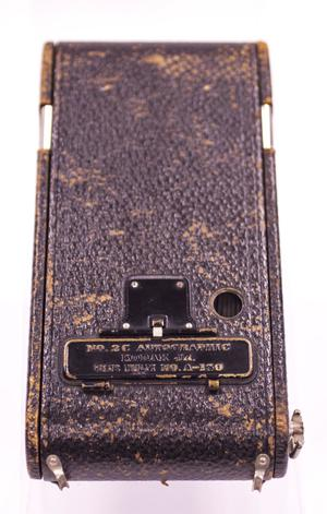 The top of a Kodak camera case. The case is a dark, worn out brown with old metal clasps on it.