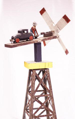 Small figure of a man standing next to a wooden truck on a tower with a windmill on it.