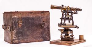 A wooden old telescope, several turning wheels at the bottom. Next to it is an old brown bag.