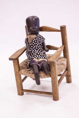 Black doll sitting in a wooden chair. The doll has on a black dress with white polka dots. Its legs are sticking out, but are short and don't extend much out of the chair.