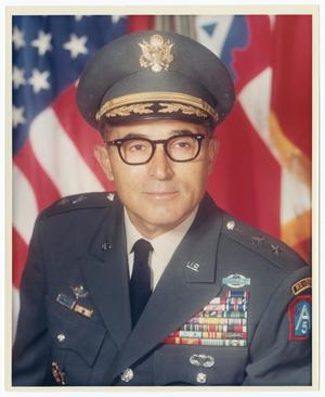 Portrait of a United States Army Major General, visible from the chest up and leaning forward toward the left side of the image. The man is dressed in his full uniform and posing in front of the American flag. His cap contains a gold emblem of an eagle front and center. His coat contains several medals and patches, including two bronze stars on each shoulder and a blue patch framed by red with a white A and 5 inside of it.
