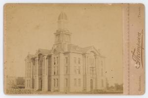 Worn out old photograph of a big white building with a protruding tower.