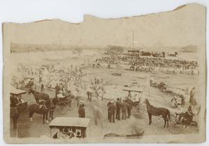 Worn out photograph. In it several men, horses, tents and other cattle can be seen. Some of the horses are pulling wagons. The top of the photograph is torn, giving it an uneven edge.