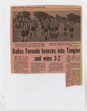 A newspaper page, with a strip of it torn on the bottom left. The top of it has a photograph of soccer refs in their uniforms. Under the picture is the title, 4 columns of text seen underneath it.