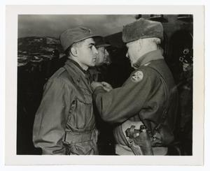 A young man in an army uniform faces an older man in uniform, who is pinning something to his uniform. There is another man on the side of him.
