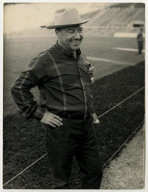 Old photograph of a man in a cowboy hat, wearing a plaid shirt and jeans. A star is seen on the left side of his shirt. His right hand is on his hip as he smiles to the side. The top right of the photograph has a slight tear on it.