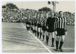 Black and white photo of several men in soccer unifrom lined up in a single file line. A crowd in the stands is seen behind them.