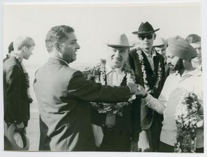 Black and white photo of a man in a suit looking torwards a man with a flower necklace and a man in a turban holding a flower necklace in his hand.