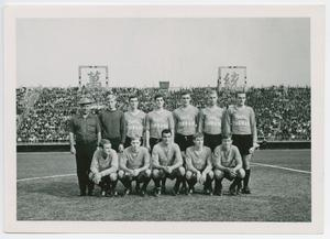 Black and white photo of 12 men in two rows. All of them wear soccer uniforms. In the back row, the two on the furthest left wear darker clothes.