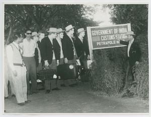 Black and white photo of a group of men standing on the left side of the photograph, with a sign on the ground next to them that reads Government of India. Another man is standing by the sign.