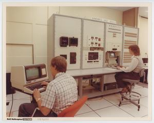 A man on the left side of the photograph is seen typing at a computer. On the right side a woman is seen typing at a computer, with another box of technology around the computer. They are in a white tiled room.