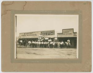 Old photograph. Several men in long white shirts and dark pants stand in front of a store. The sign says Drug Store. On the right side is a wagon pulled by a horse.