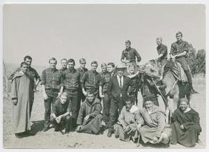 A black and white photograph with several men standing next to each other. On the right side of the photo, 2 men are seen on a camel.