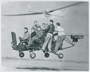 A black and white photograph of seven men on a black helicopter model that is a few feet above the ground.
