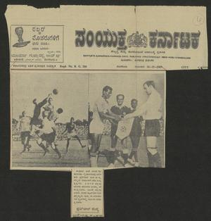 A newspaper page, parts of it cut out on the right side and bottom of the it. It is in the Kannada language. The main part of the page is 2 photos side by side. The left side is a soccer game in action, the right side is of 2 men standing in front of each other, a banner being passed between them.
