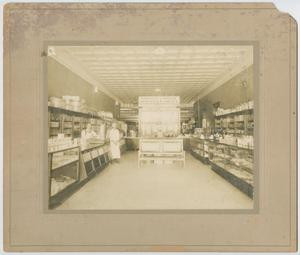 Worn out photograph with a yellowish tint. The picture is of a merchandise store. A man can be seen towards the back on the left side of the picture. On both sides are two rows of stuff, with an empty aisle in the middle.